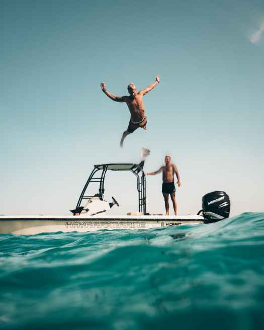photo of man jumping from boat to the sea