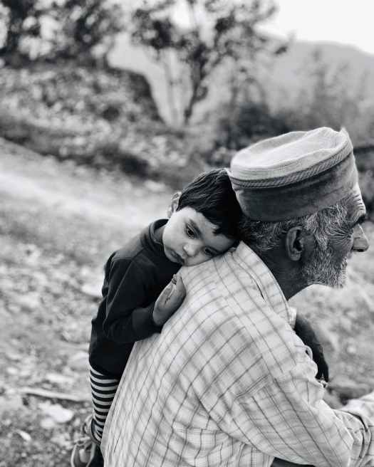boy leaning beside an old man